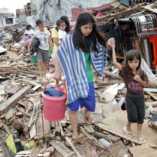 Two girls walk through the destruction caused by Typhoon Haiyan in the Philippines Photo: Caritas Internationalis