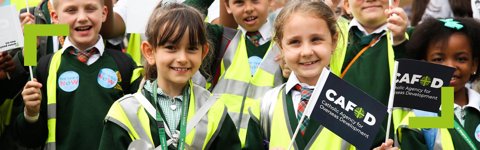 School children wave CAFOD flags at the Time is Now mass lobby on climate change.