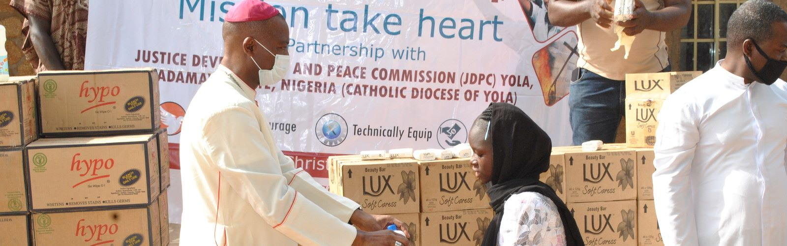 A bishop gives a hygiene kit to a family