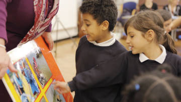 Children looking at CAFOD's big book resource available from the CAFOD shop