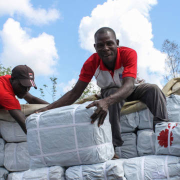Two men unload aid packages from a lorry