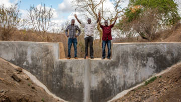 Project members celebrate on top of one of the new sand dams that the community have built.