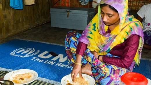 Saba eats food in her shelter in a refugee camp in Bangladesh