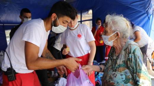 A member of Caritas Lebanon hands out a bag of essentials to a local elderly lady in Beirut.