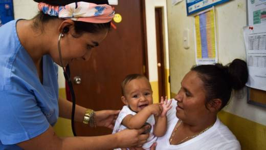 Blanca and her daughter at the Ana Manganaro clinic. The baby is having her heart listened to with a stethoscope