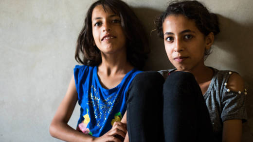 Majid's eldest daughter Raisa, age 11, and her younger sister sit in their rented home in Syria