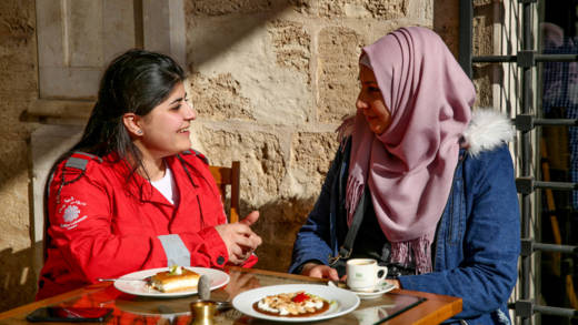 Two young women from different backgrounds sit together in a cafe