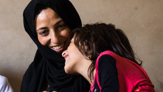 Dana smiles at one of her daughters who leans in close to her mother
