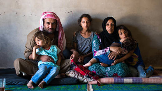 Majid sits with his wife and four of his daughters in his rented home