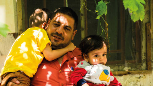 Kadar holds two of his small children outside their home in Syria