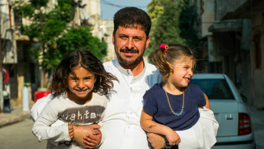 Marwan smiles and stands holding his two young children in the street in Syria