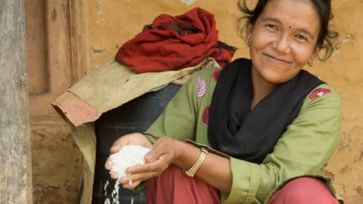 Woman in Nepal with a handful of rice