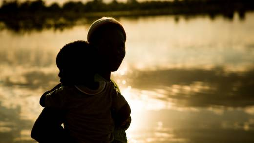 Memory with her baby near water in Zimabwe- CAFOD Lent
