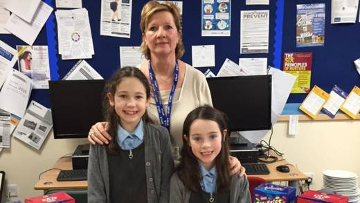 Amy and Hannah stand smiling with a teacher at their school where they organise a raffle for CAFOD
