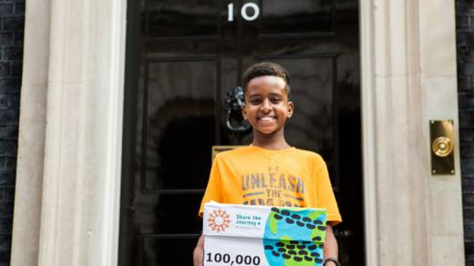 A boy stands outside number 10 Downing Street holding a CAFOD petition to hand to Prime Minister Theresa May