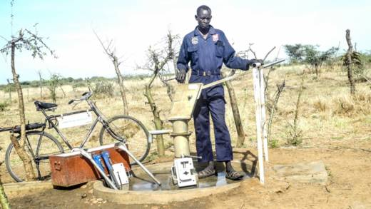 Raphael at a borehole in Uganda with his bicycle