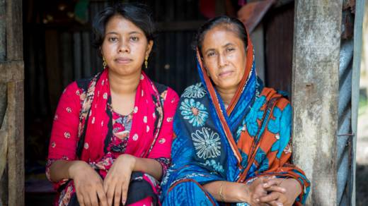 Nomita and her daughter Sonia sit in the doorway of their home in Bangladesh