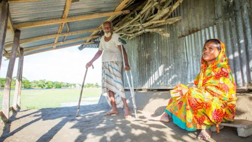 Mahinur and Khalek on the porch outside their home in Bangladesh. Khalek is standing with the help of crutches.