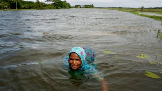 Mahinur swimming in the river trying to catch fish with her net