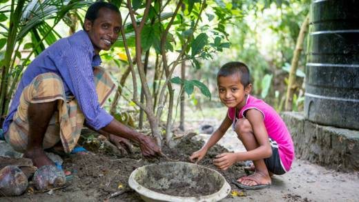 Suchandra and his son look after saplings they have grown in their garden. They are smiling and happy