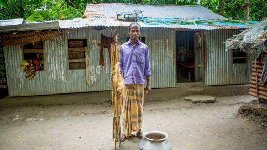 Suchandra stands outside his home in Bangladesh which was badly damaged in Cyclone Mahasen in 2013