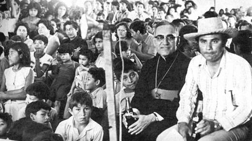 Saint Oscar Romero sits with a large group of people in El Salvador