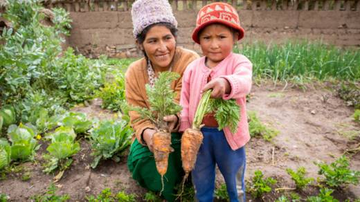 Rosa and her youngest daughter hold up the large carrots that they have just picked from the garden