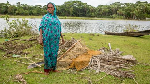 Mahinur stands beside her fishing net on the bank of the river by her home in Bangladesh