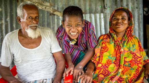 Mahinur sits with her husband and son. Her son Rabiul is laughing and Mahinur smiles with him.