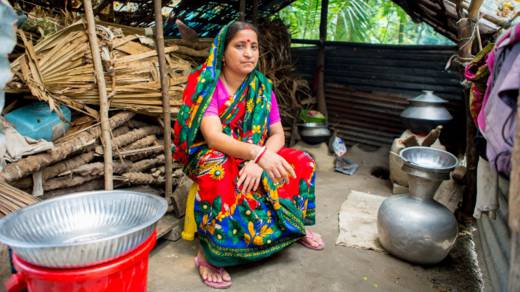 Monica sits on a stool in her kitchen in Bangladesh. She got into debt rebuilding her home after it was damaged by a cyclone