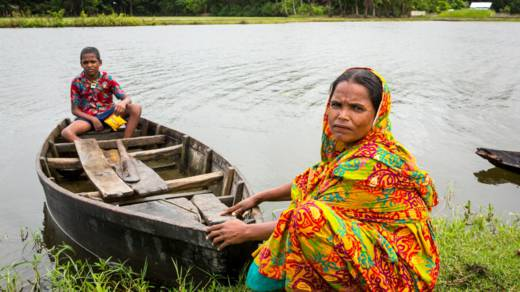 Mahinur and her son Rabiul in their boat on the river outside their house in Bangladesh