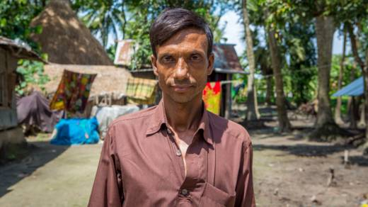 A community leader stands in the middle of his village in Bangladesh.