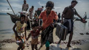 A group of Rohingya refugees, including children, help each other ashore after crossing the river from Myanmar into Bangladesh