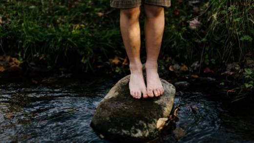 Bare feet on a stone in the lake.