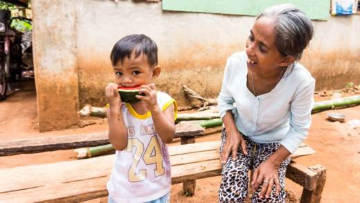 A child in the Philippines is watched by a smiling adult as he bites into a slice of watermelon