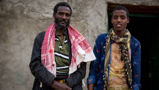 Father, Adam Ali, and son, Mohammed, stand outside a house in Ethiopia, looking at the camera