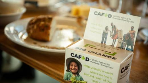 A CAFOD moneybox is in the foreground, with soup and bread in the background