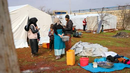 Displaced people stand outside tents