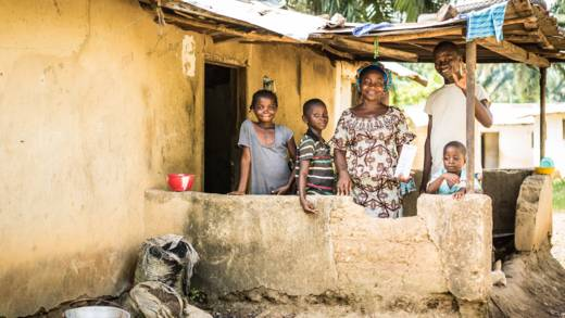 Garmah and her children outside their house in Liberia