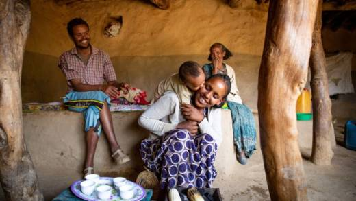 3 adults and a child, all happy, inside a house in Ethiopia.