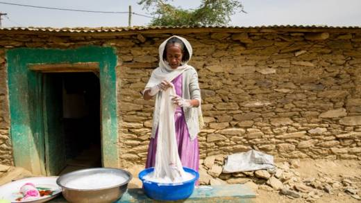 Almaz using bowls of soapy water to wash fabrics