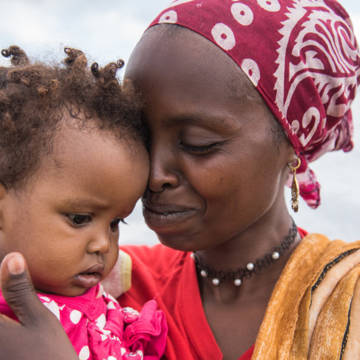 Amina with her child in a refugee camp