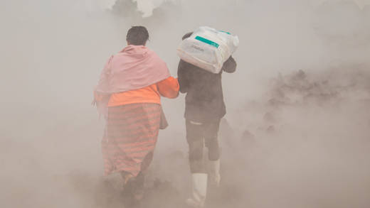 Two people walking, surrounded by smoke. One is carrying a sack and offering a hand to the other.