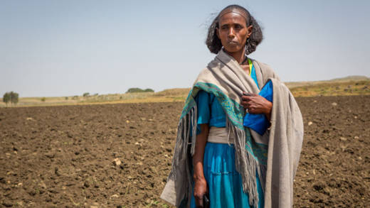 Herit, a farmer from Ethiopia, standing in a field she has ploughed