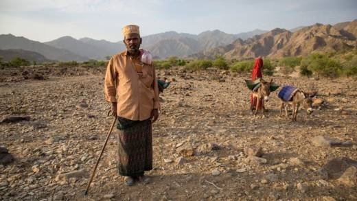 A man holding a cane stands in the Ethiopian desert