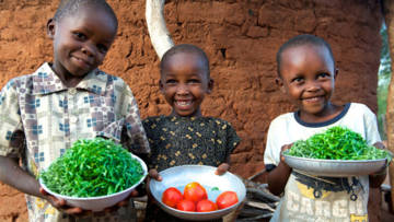 Muvwithi, Sabina,and Joseph with tomatoes and greens