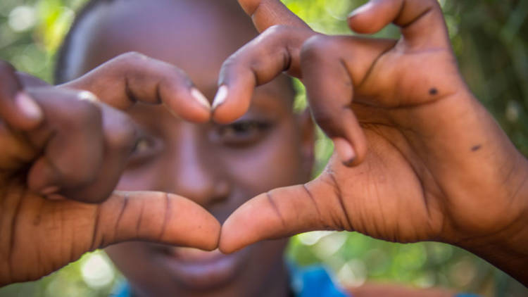 A young girl in Kenya makes the shape of a heart with her fingers