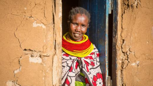 Mary prays outside her home in Kenya CAFOD