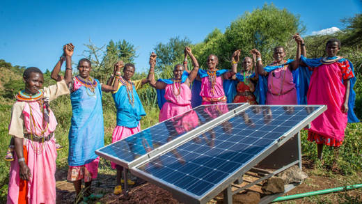 Women in Kenya celebrate installing a solar pannel which will provide power for schools, clinics and irrigation systems and will help tackle climate change.