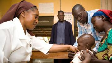Nigerian nurse helping a child